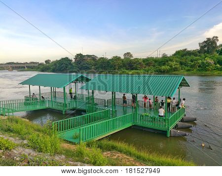 KHANCHANABURI THAILAND-APRIL 13, 2017 : People stay on the houseboat for fish feeding at Mae Khlong River, Khanchanaburi, Thailand.