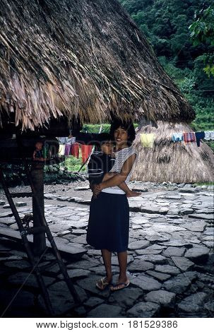 BANAUE, IFUGAO / PHILIPPINES - CIRCA 1990: An Ifugao woman holds her small child and poses for a photograph outside a home near Banaue.