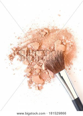 Make-up brush and crushed face powder. Isolated on white