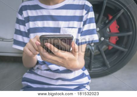 woman hand holding and using mobile on car background concept calling mechanic service from repair shop. vintage effect