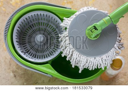 Used round spin mop with microfiber head, green handle on cleaning bucket next to floor cleaning liquid with blurred yellow tiles