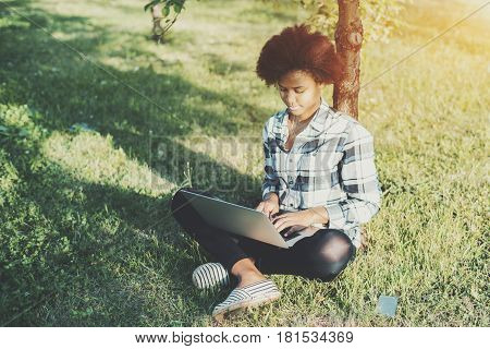 Attractive young black female student working on laptop while sitting crossed-legs on grass in park beautiful mixed teenage girl with curly afro hair sitting on summer meadow and using her net-book