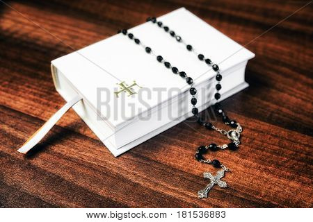 White prayer book and black rosary on the table