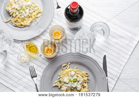 Plates of delicious pasta alfredo with chicken on served table