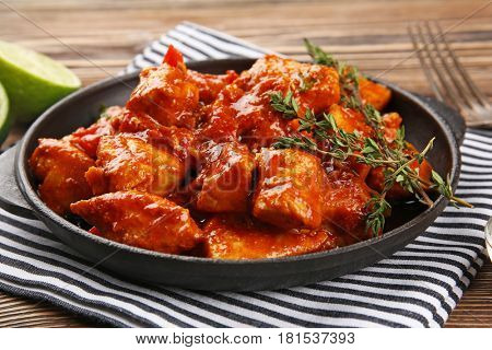 Frying pan with delicious chicken tikka masala on napkin