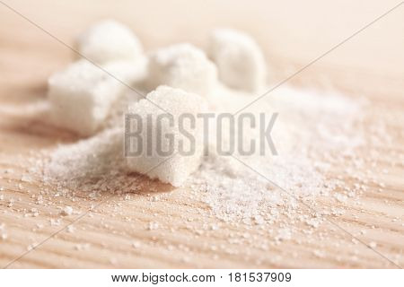 Granulated sugar and cubes on wooden background