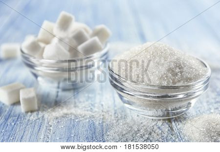 Glass bowls full of lump and sand sugar on wooden background