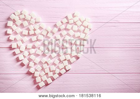 Sugar cubes arranged in shape of heart on color wooden background