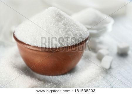 White sand and lump sugar with bowl on wooden background