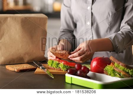 Mother preparing sandwich for school lunch on table