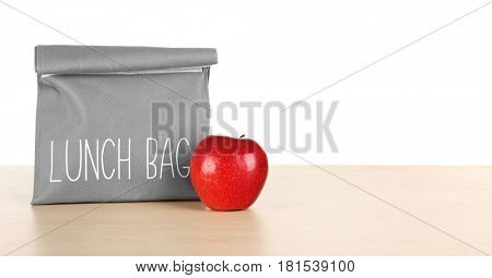 Lunch bag with apple on wooden table against white background