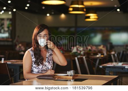 Portrait of beautiful woman drinking cappuccino in cafe
