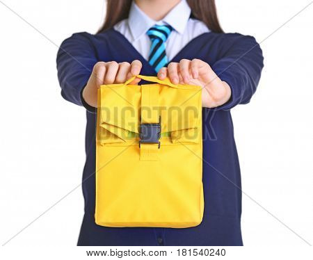 Cute schoolgirl with lunch bag on white background