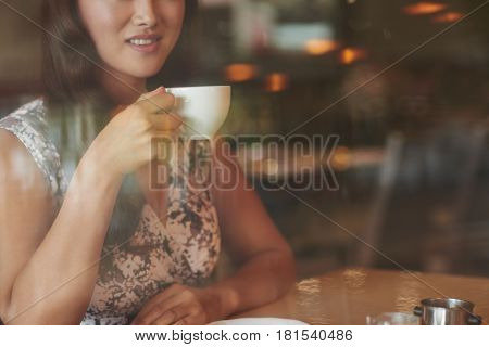 Cropped image of young woman drinking cup of coffee
