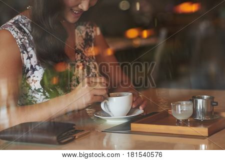 Cropped image of young woman mixing sugar in her coffee