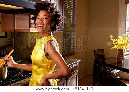 Happy African American woman cooking in the kitchen.