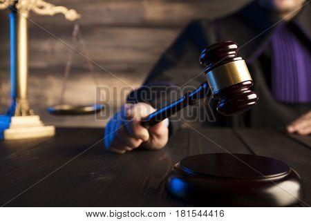 Law theme and concept. Mallet in the hand of judge in toga.