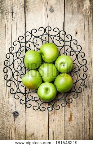 apples in a bowl on wooden background and