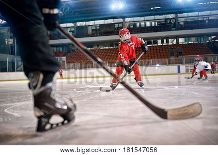 Hockey match at rink player in action kicking on goal