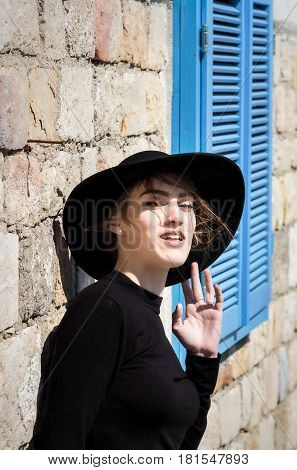 Expressive beautiful young woman in black with black hat looking at the camera