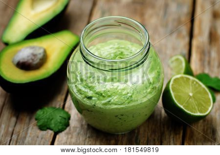 Greek yogurt avocado cilantro lime dressing on wood background