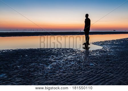 An Iron Man on the edge of a pool of water along Crosby beach.