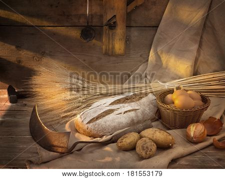 Still life with a sickle bread ears of wheat potatoes onion tools wooden background light rustic style rustic sunlight shadows