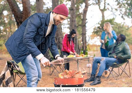 Man Kindling Fire On Grill