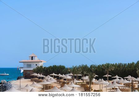 Luxury hotel resort place at sea shore with wicker umbrellas parasols or sunshades tropical green palm trees on bright sunny day on blue sky background. Idyllic summer vacation copy space