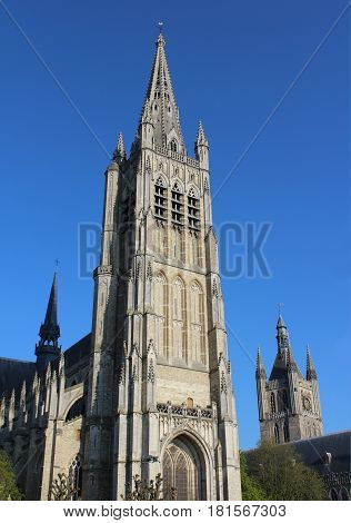 Exterior view of the beautiful St. Maartens Cathedral, in Ieper, Belgium, lit by the evening sun against a background of blue sky.