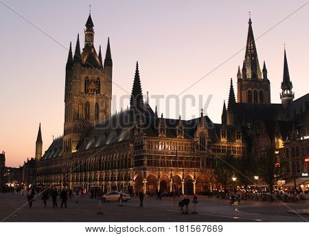 IEPER, BELGIUM, APRIL 8 2017: Sunset behind the beautiful landmarks of the Cloth Hall and St Martins church in Ieper. The town is a hugely popular tourist destination and a focus of war remembrance.