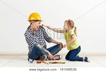 Laughing young mother in hardhat with cute little girl holding paint brush. Concept of room remodeling and improvement.