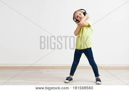 Studio portrait of adorable small girl listening pop music in earphones. Little cutie enjoying loud sound.