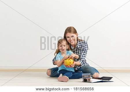 Smiling mother with her little daughter sitting on the floor with piggybank, collecting cash for new housing. Concept of family economy and ownership.
