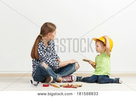 Renovation of new realty. Young woman with little daughter in helmet ready to color empty room.