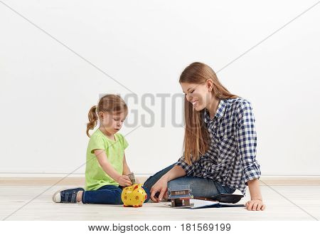 Family savings concept. Young woman with her little daughter planing new flat purchase, sitting on the floor with piggy bank and house model.