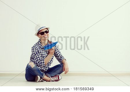 Woman dreaming of summer vacation. Young female in casual outfit throwing paper plane in the room with space for text.