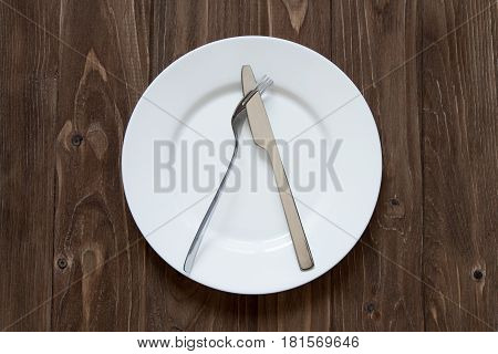 Plate and cutlery on wooden background in dislike form, top view