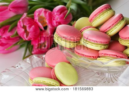 A french sweet delicacy macaroons variety closeup.macaroon colourful texture. Sweet macarons and flowers.