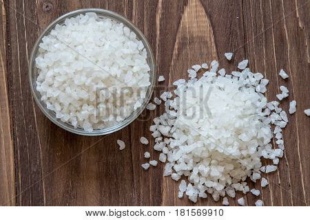 Sea salt in glass bowl and pule on wooden background, top view