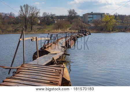 Landscape with pontoon-bridge over small river Sura to remote Ukrainian village Rakshivka