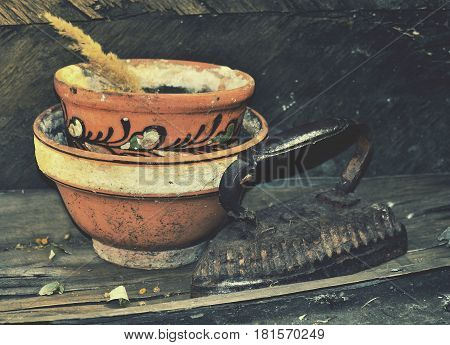 Vintage pot and iron with old background.Image with a feeling of abandonment and discarding