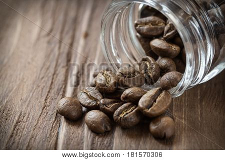 Cofee beans pulled out of glass jar, close-up