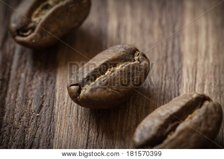 Roasted cofee beans macro on wooden background, close-up