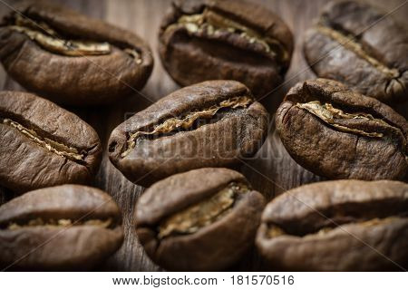 Few roasted cofee bean on wooden background, close-up