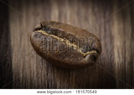 One roasted cofee bean isolated on wooden background, close-up, macro