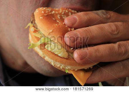 A Man eating a fresh made hamburger