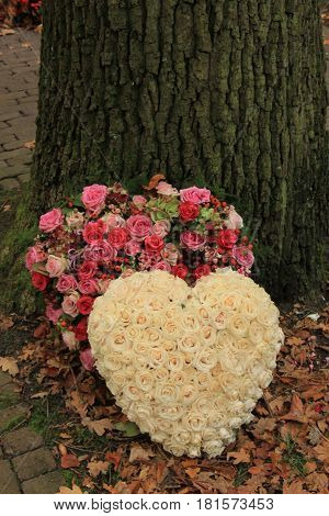 sympathy or funeral flowers near a tree