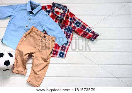 Baby boy clothing set (blue shirt plaid red shirt and brown pant). Wish list or shopping overview for pregnancy and baby shower. View from above.