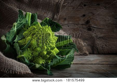 Romanesco broccoli or Roman cauliflower on a rustic wooden background with copy space the healthy vegetable Brassica oleracea is a variation of cauliflower bred near Rome selective focus